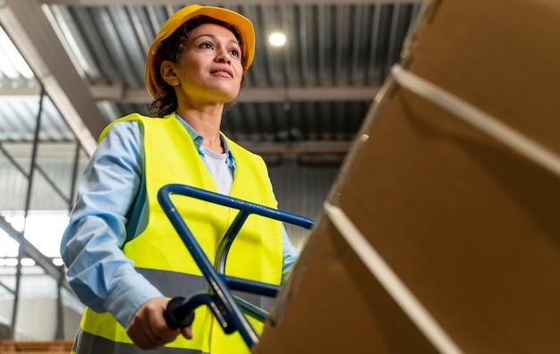 Kobieta z kaskiem do przenoszenia pudeł