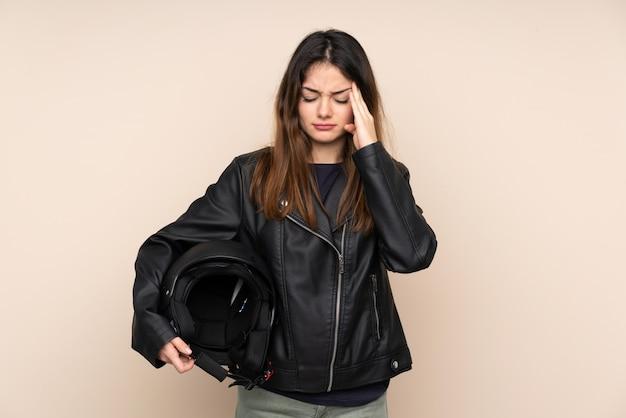 Kobieta z kaskiem motocyklowym na beżowym tle niezadowolony i sfrustrowany czymś. negatywny wyraz twarzy