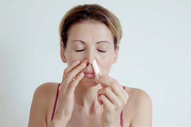 Kobieta z katarem siennym rozpyla krople do nosa, aby wspomóc oddychanie