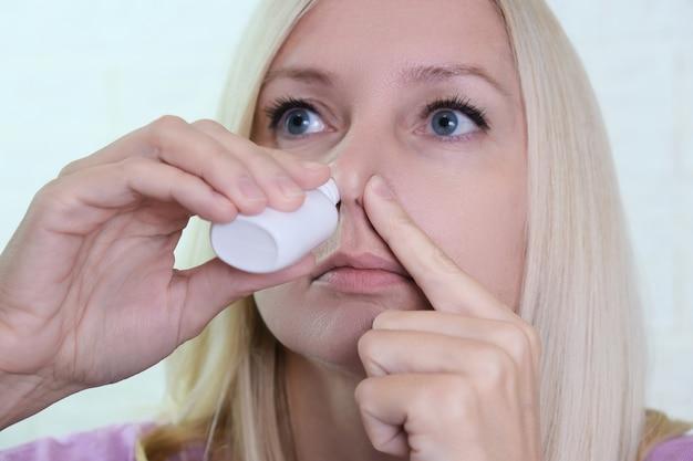 Kobieta z katarem trzyma w dłoni lekarstwo, iryguje sprayem do nosa, aby zatrzymać alergiczny nieżyt nosa i zapalenie zatok.