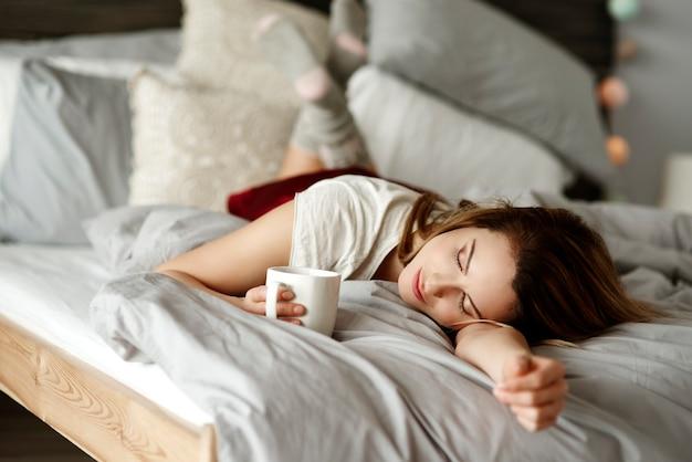 Kobieta z kawą leżącą w łóżku