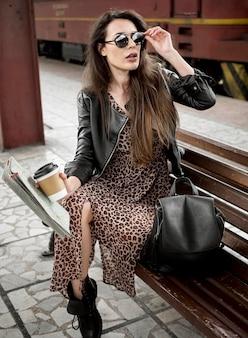 Kobieta z kawą na ławce przy dworcem