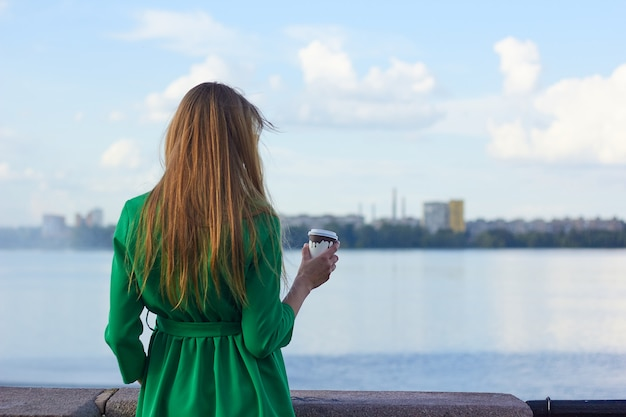 Kobieta z kawą oglądając w rzece