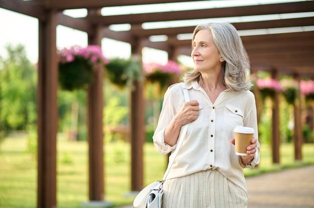 Kobieta z kawą patrząca na bok w parku