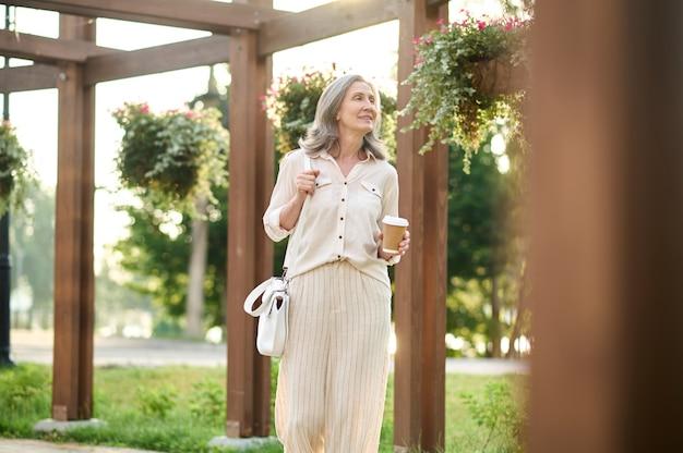 Kobieta z kawą patrząca na kwiaty w parku