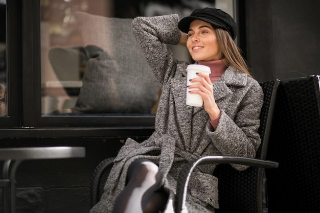 Kobieta z kawowym obsiadaniem na zewnątrz kawiarni