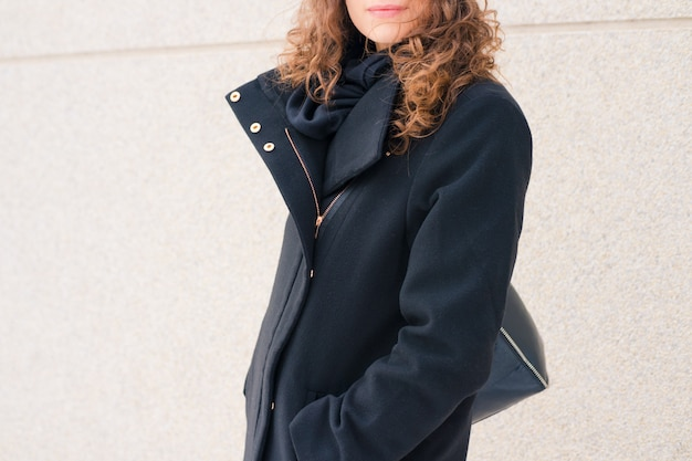Kobieta z kędzierzawym włosy w czarnym żakiecie na tle beżowa ściana