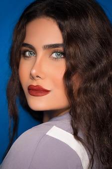 Kobieta z kędzierzawymi włosami na błękitnym tle