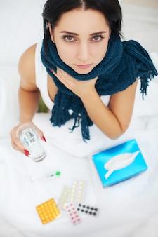 Kobieta z kichającym nosem używająca chusteczki na łóżku cierpiąca na wirusa przeziębienia i leki