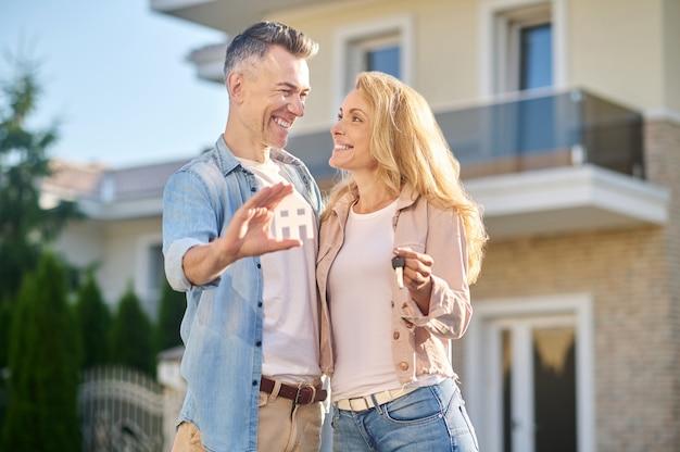 Kobieta z kluczami patrząca na męża ze znakiem domu