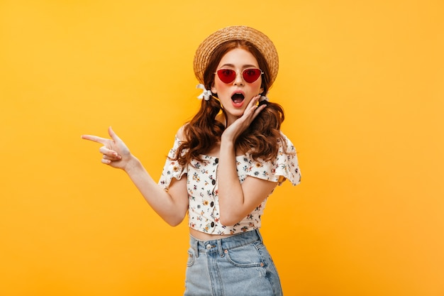 Kobieta z kokardkami na włosach i kapeluszu wygląda na zdumioną. kobieta w czerwonych okularach przeciwsłonecznych i denimowej spódnicy wskazuje palcem na pojedyncze tło.