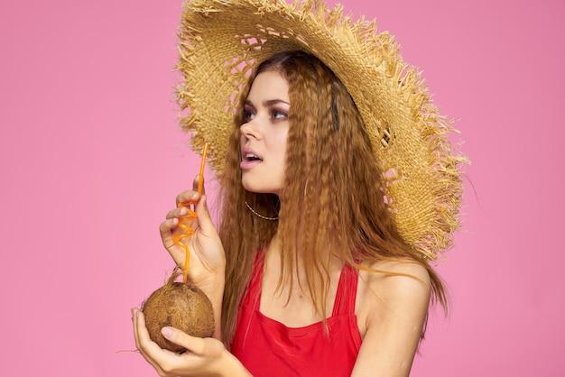 Kobieta z kokosowym koktajlem w słomkowym kapeluszu egzotyczne wakacje lato i różowe tło