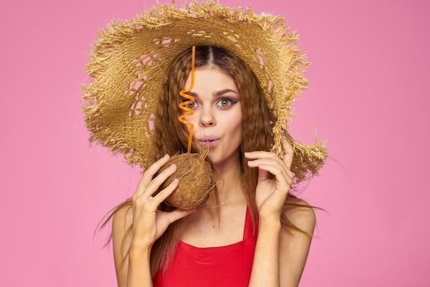 Kobieta z kokosowym koktajlem w słomkowym kapeluszu egzotyczne wakacje letnie różowe tło.