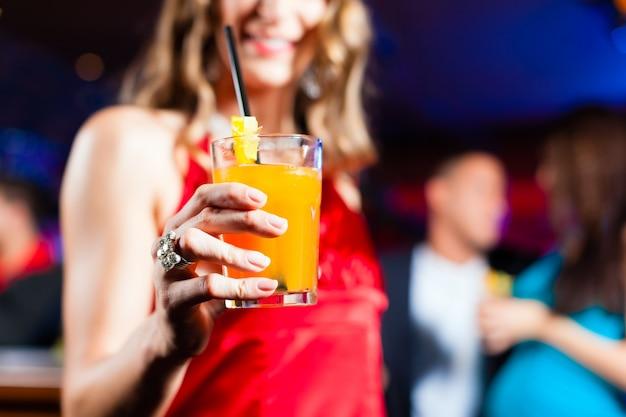 Kobieta z koktajlem w barze lub klubie