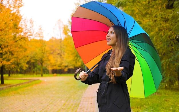 Kobieta z kolorowym parasolem sprawdzanie deszczu w parku miejskim
