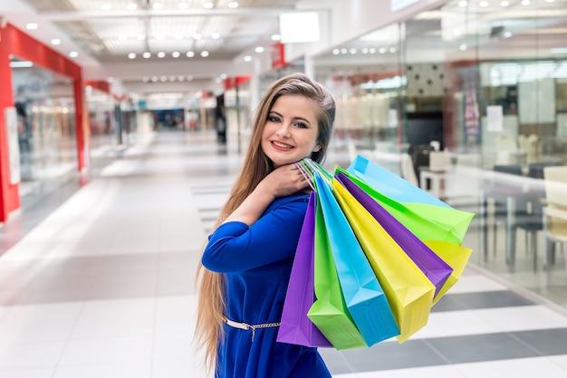 Kobieta z kolorowymi torbami na ramieniu na zakupy