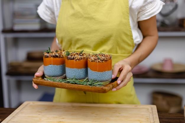 Kobieta z kolorowymi, zdrowymi, słodkimi deserami puddingami chia z mlekiem migdałowym, ekstraktem z niebieskiej spiruliny, nasionami chia, dżemem pappaya mango i domową mueslią. na drewnianym stole w kuchni w domu.