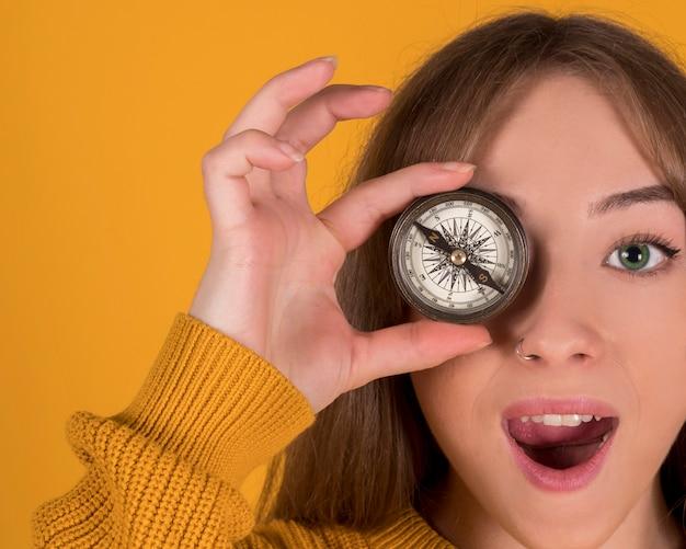 Kobieta z kompasem zakrywającym jej oko, zdziwiona twarz, odizolowywająca na żółtym tle