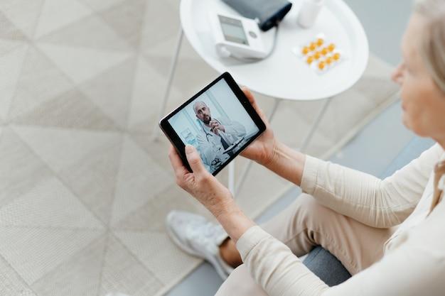 Kobieta z komputerem typu tablet podczas konsultacji online z lekarzem