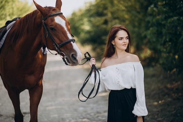 Kobieta z koniem w lesie
