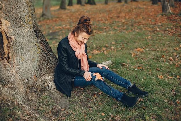 Kobieta z kontuzją nogi. ranna dziewczyna siedząca przy drzewie. rana krwawi.