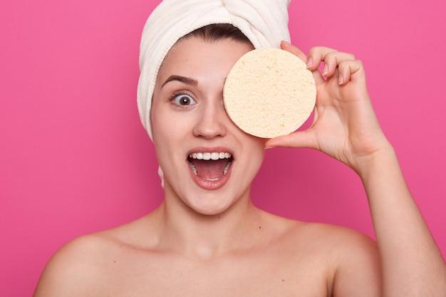 Kobieta z kosmetyczną gąbką zakrywającą jedno oko, owinięta białym ręcznikiem, kobieta o doskonałej skórze