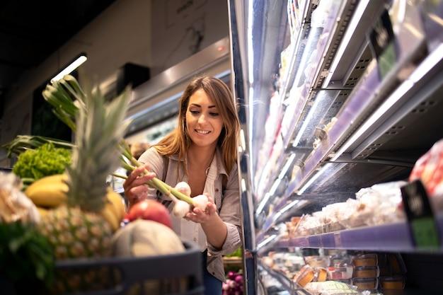 Kobieta z koszykiem kupuje jedzenie w supermarkecie.