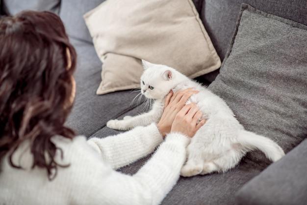 Kobieta z kotem. młoda ciemnowłosa kobieta spędza czas z białym kotem w domu