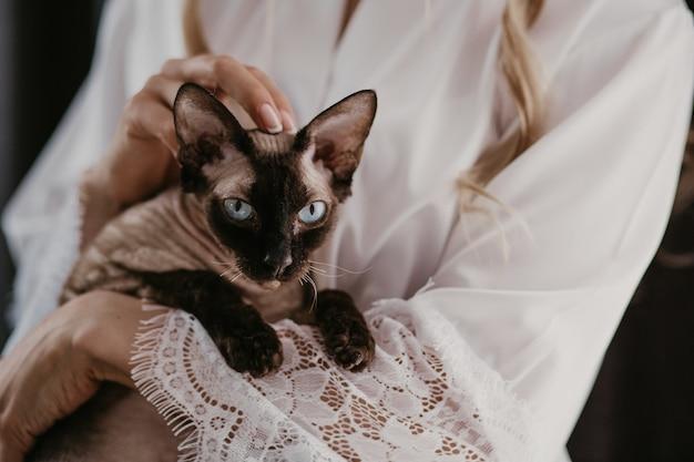 Kobieta z kotem sphynx w dłoniach