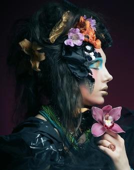 Kobieta z kreatywnych makijaż gospodarstwa różowy kwiat