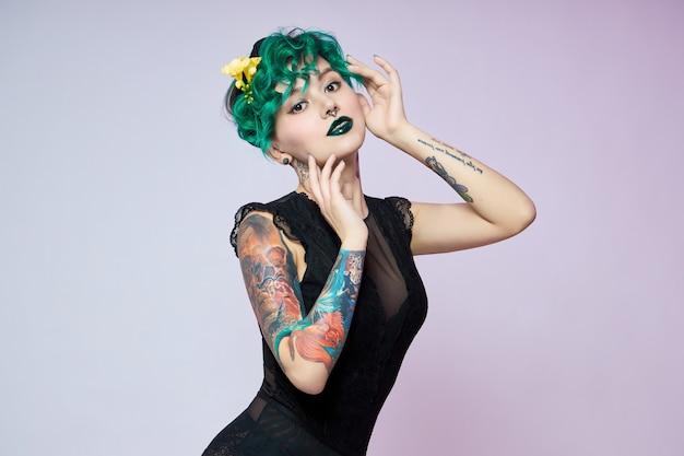 Kobieta z kreatywnym zielonym farbowaniem włosów i makijażu, toksycznymi kosmykami włosów. jasny kolor kręcone włosy na głowie dziewczyny, profesjonalny makijaż