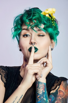 Kobieta z kreatywnym zielonym farbowaniem włosów i makijażu, toksycznymi pasmami włosów. jasny kolor kręcone włosy na głowie dziewczyny, profesjonalny makijaż. kobieta z tatuażem