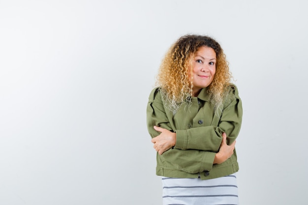 Kobieta z kręconymi blond włosami przytulająca się w zielonej kurtce i wyglądająca na zawstydzoną. przedni widok.
