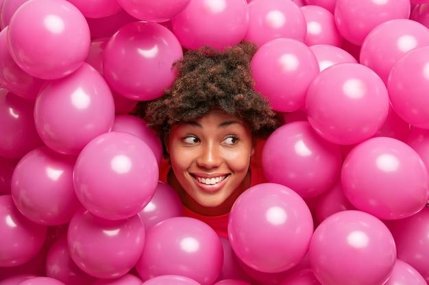 Kobieta z kręconymi, krzaczastymi włosami uśmiecha się szeroko, wygląda dobrze, ma świąteczny nastrój pozuje wokół napompowanych helowych balonów