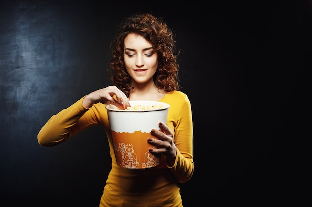 Kobieta z kręconymi włosami bierze trochę popcornu, gryząc jej pośladki