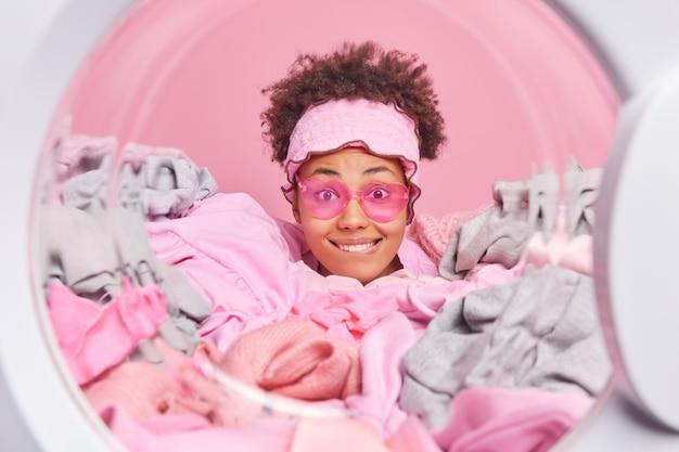 Kobieta z kręconymi włosami gryzie wargi z radością patrzy w kamerę, szczęśliwa kończąc prace domowe, nosi modne okulary przeciwsłoneczne, wtyka głowę przez stos prania pozuje w pralce