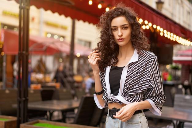 Kobieta z kręconymi włosami na ulicy
