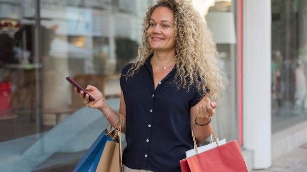 Kobieta z kręconymi włosami, niosąc torby na zakupy