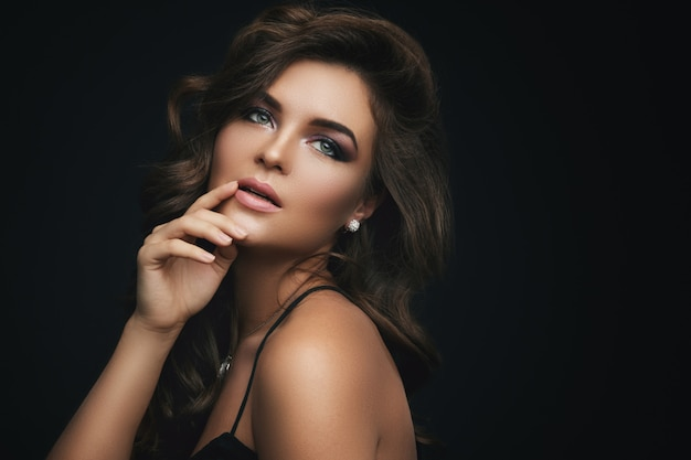 Kobieta z kręconymi włosami, pięknym makijażem i drogim wisiorkiem z dimondem