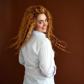Kobieta z kręconymi włosami portret pięknej wesołej rudej dziewczyny z rozwianymi kręconymi włosami uśmiechniętymi śmiechem