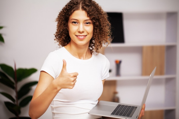 Kobieta z kręconymi włosami pracuje na laptopie w biurze.