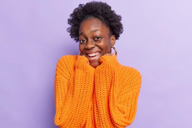 Kobieta z kręconymi włosami trzyma ręce pod brodą, uśmiecha się pozytywnie, pokazuje białe zęby ma dobry nastrój, nosi powiększony pomarańczowy sweter z dzianiny na fioletowym tle