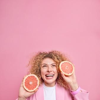 Kobieta z kręconymi włosami trzyma świeże plasterki grejpfruta, uśmiecha się szeroko ubrana, formalnie skoncentrowana nad głową