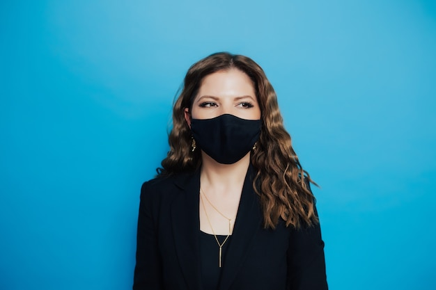 Kobieta z kręconymi włosami ubrana w czarną maskę na niebieskim tle