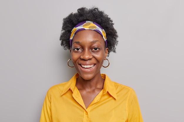 Kobieta z kręconymi włosami uśmiecha się przyjemnie nosi opaskę na głowę żółta koszulka wygląda optymistycznie stoi na szaro