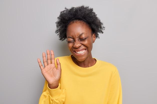 Kobieta z kręconymi włosami uśmiecha się ząbkowo unosi dłoń wita przyjaciela nosi swobodny żółty sweter na szarym tle