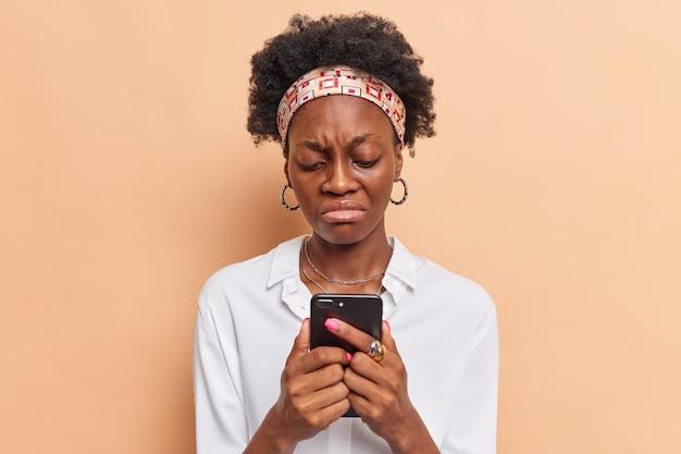 Kobieta z kręconymi włosami używa nowoczesnych telefonów komórkowych, wysyła wiadomości tekstowe, nosi opaskę na głowie, białą koszulę, zdenerwowana, że nie ma wystarczającej ilości pieniędzy na koncie bankowym w aplikacji na smartfona