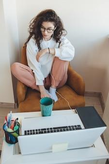 Kobieta z kręconymi włosami w okularach prowadzi w domu lekcje online przy laptopie i pijąc herbatę