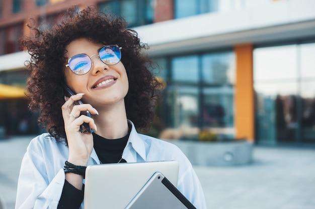 Kobieta z kręconymi włosami w okularach rozmawia przez telefon podczas pozowania ze swoim laptopem