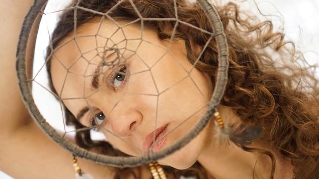 Kobieta z kręconymi włosami z łapaczem snów w dłoni przed twarzą